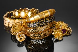 cash for gold: Beautiful golden bracelets, rings and jewelry on grey background, twerys